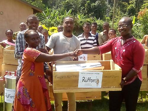 A beehive being handed over by Mr. Richard Boakye to Mary Arthur, a project beneficiary.