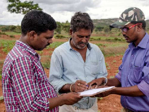 Wild Seve field assistant (right) using the pen and paper method to record villagers' complaints of crop damage by wildlife. Data are now recorded electronically. ©CWS.