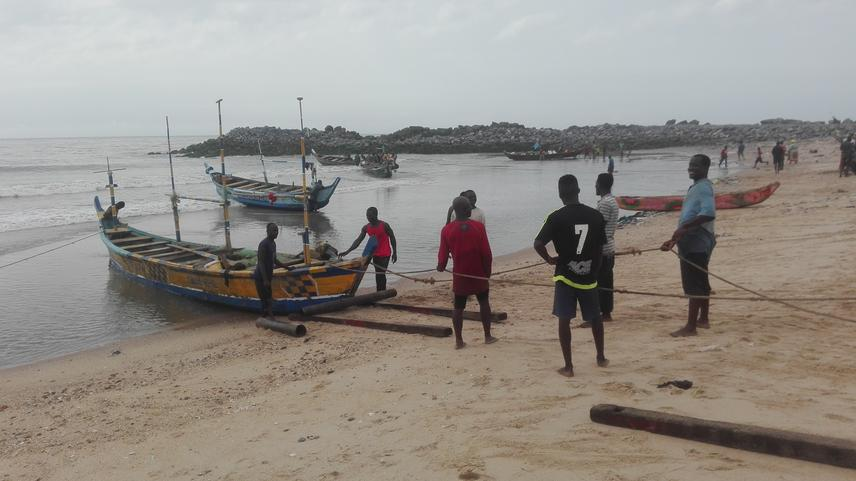 Project team member interactin with fishermen at Jamestown while helping them pull their net.